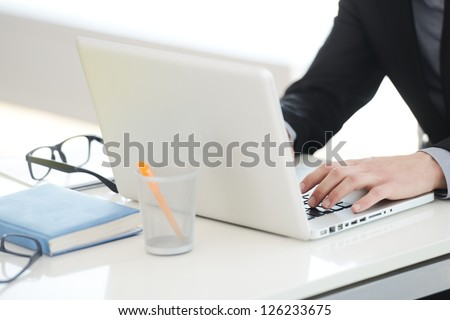Businessman working on laptop, hands typing