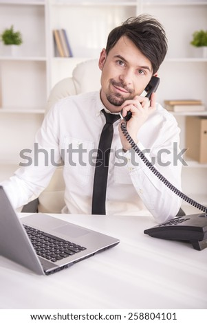 Businessman working on laptop, looking at the camera  and holding a phone