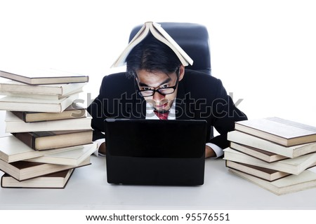 Businessman working on laptop with a book on his head - stock photo