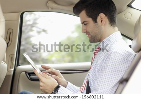 Businessman working on tablet in his car - stock photo