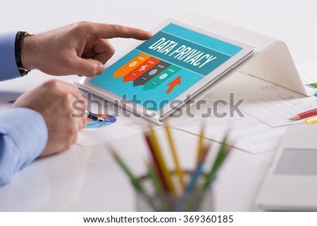 Businessman working on tablet with DATA PRIVACY on a screen - stock photo