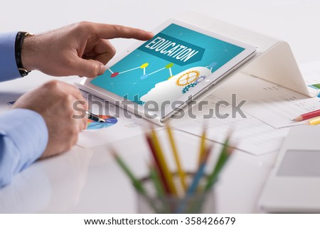 Businessman working on tablet with EDUCATION on a screen - stock photo