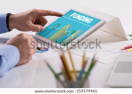 Businessman working on tablet with FUNDING on a screen - stock photo