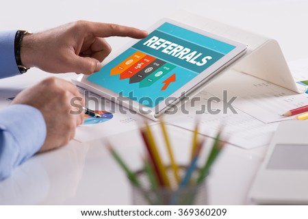 Businessman working on tablet with REFERRALS on a screen - stock photo