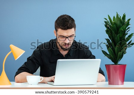 Businessman working on the laptop computer in office - stock photo