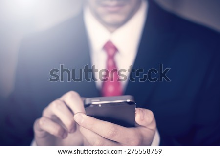 Businessman working on the smartphone - stock photo