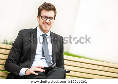 Businessman working outdoor while sitting on a bench