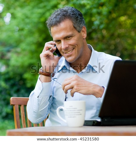 Businessman working outdoor with mobile and laptop - stock photo
