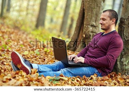Businessman working outdoors on his laptop, in a beautiful forest - stock photo