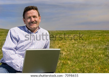 Businessman working outdoors with laptop - stock photo