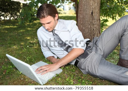 Businessman working outside on laptop - stock photo