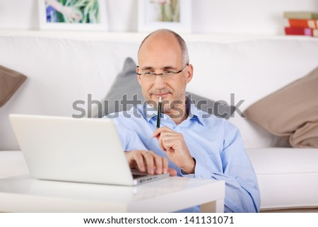 Businessman working through his laptop while leaning on the couch - stock photo