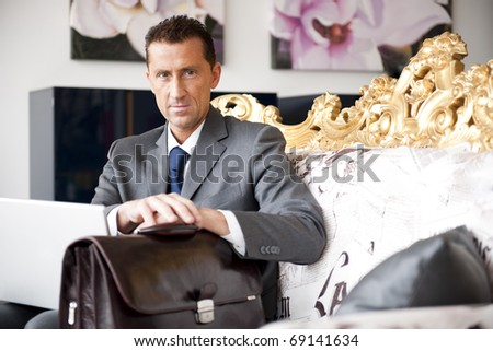 Businessman working while sitting on a vintage sofa - stock photo