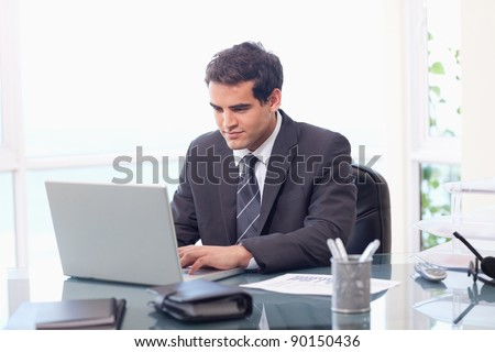 Businessman working with a laptop in his office - stock photo