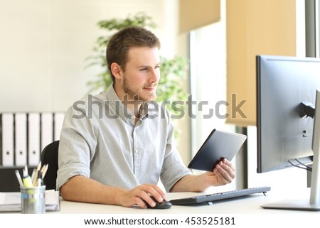 Businessman working with a tablet and desktop computer on line in the office
