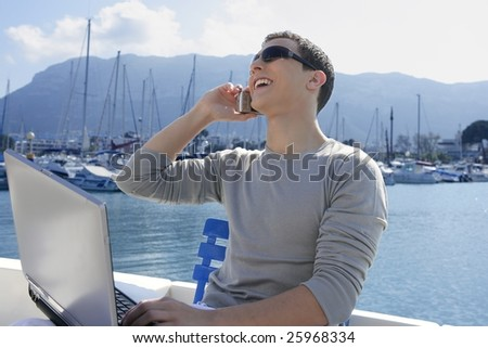 Businessman working with computer on a boat, nice outdoor office - stock photo