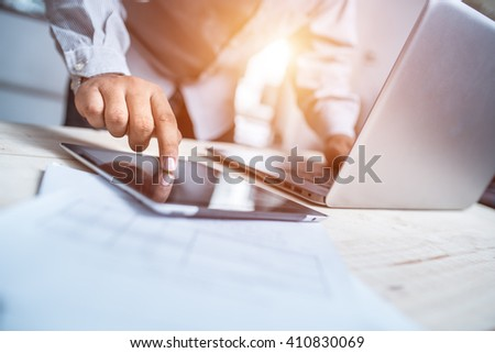 businessman working with digital laptop computer and smart phone with digital business strategy layer effect on wooden desk as concept