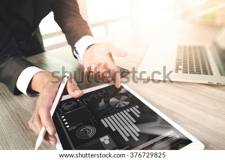 businessman working with digital tablet computer and smart phone and laptop computer with financial business strategy layer effect on wooden desk as concept - stock photo