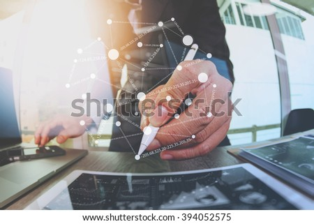 businessman working with digital tablet computer and smart phone with financial business strategy layer effect on wooden desk as concept - stock photo