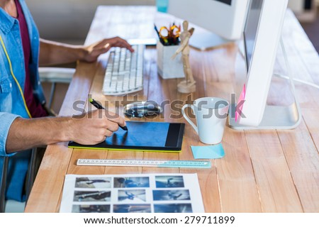 Businessman working with digitizer at his desk in the office - stock photo