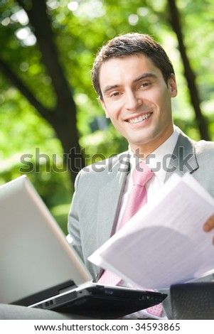 Businessman working with laptop and documents, outdoor