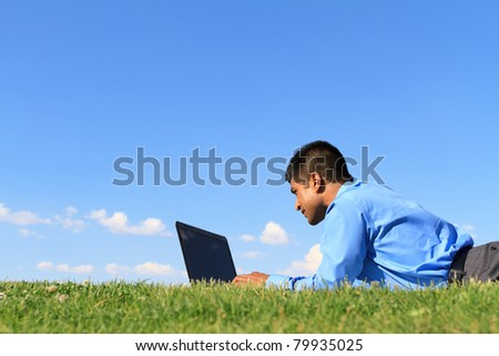 businessman working with laptop at the park