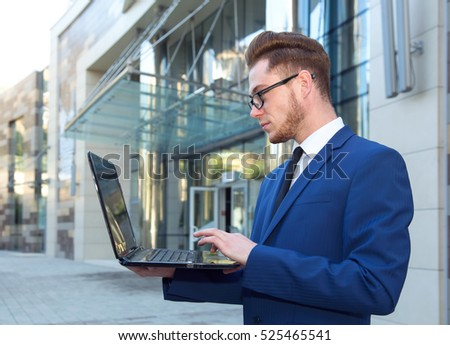 Businessman working with laptop. Employee looking at computer monitor.