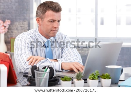 Businessman working with laptop, sitting at desk, typing on keyboard. - stock photo