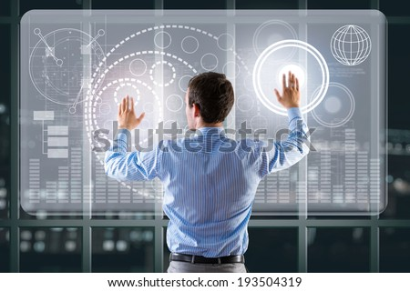 businessman working with modern virtual technologies, stands back, hands touching the screen