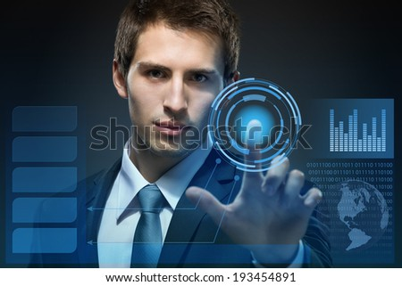Businessman working with modern virtual technology pressing keys on touch screen on black background - stock photo
