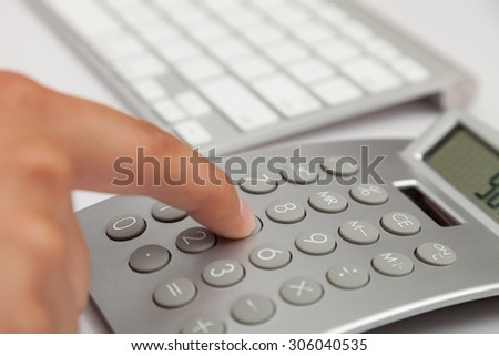 Businessman working with PC and calculator - stock photo