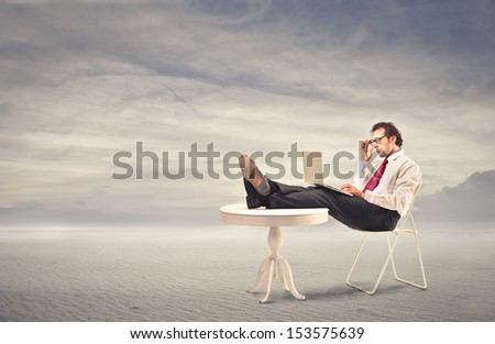businessman working with tablet comfortable sitting with feet on the table in the desert - stock photo