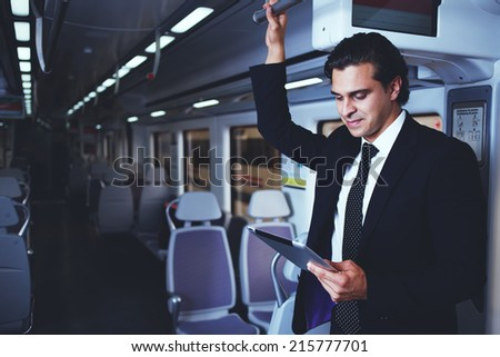 Businessman working with tablet on the way to work in train, attractive businessman in suit using technology, mature man holding digital tablet - stock photo