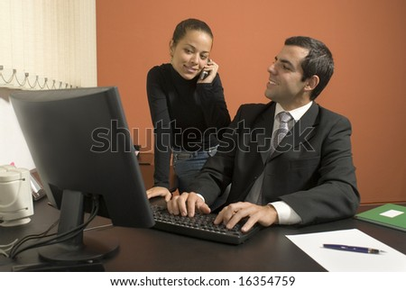 Businessman works on his computer as his secretary speaks on her phone. Horizontally framed photo. - stock photo