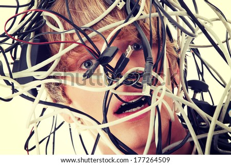 Businessman wrapped in computer cables - stock photo