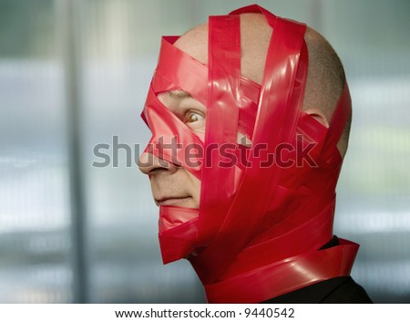 Businessman wrapped in red tape - stock photo