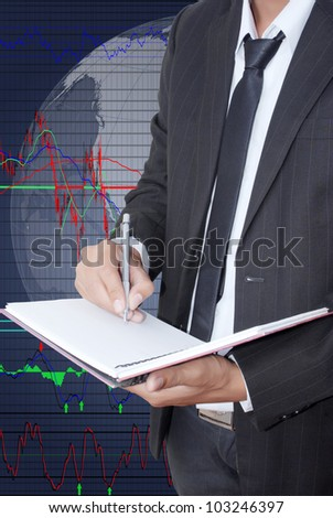 Businessman write on notebook for trade stock market graph.