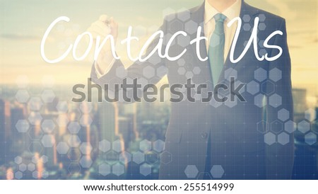 businessman write on transparent board Contact Us with sunset over the city in the background, the sun's rays falling into lens are symbolizing the good attitude - stock photo