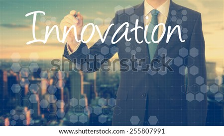 businessman write on transparent board Innovation with sunset over the city in the background, the sun's rays falling into lens are symbolizing the good attitude - stock photo