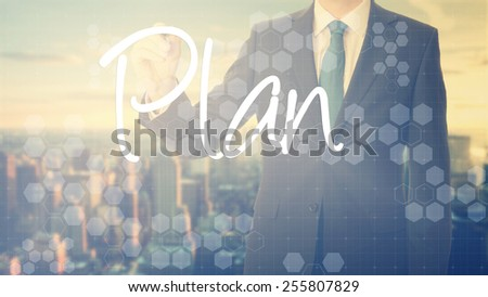 businessman write on transparent board Plan with sunset over the city in the background, the sun's rays falling into lens are symbolizing the good attitude - stock photo