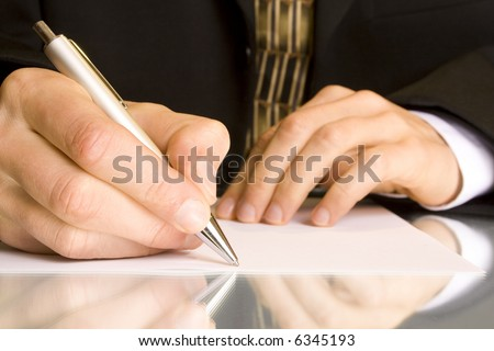 Businessman writes a pen on an empty paper - stock photo