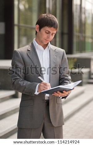 Businessman writes in a notebook
