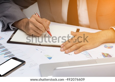 Businessman writes in a notebook with early sun light at a morning.