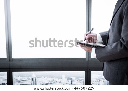 businessman writes in datebook