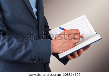 Businessman writes notes in the diary, close up