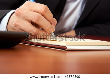 Businessman writing a document in his office - stock photo