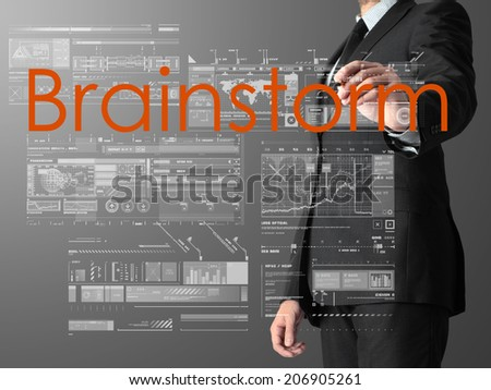 businessman writing Brainstorm and drawing graphs and diagrams on grey background - stock photo
