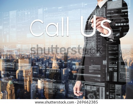 businessman writing Call Us on transparent board with city in background  - stock photo