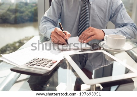 Businessman writing down his ideas - stock photo
