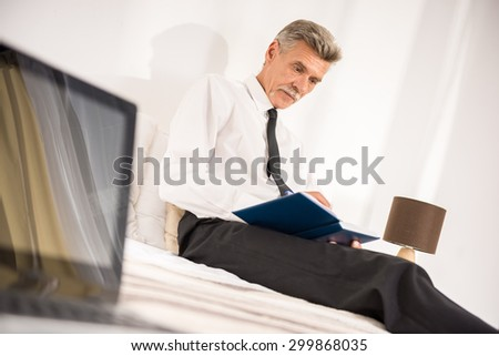 Businessman writing down his notes at notebook while sitting on bed at the hotel room. Side view.